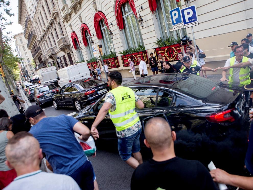 Un grupo de taxistas increpando a un coche frente al hotel Palace de Barcelona.