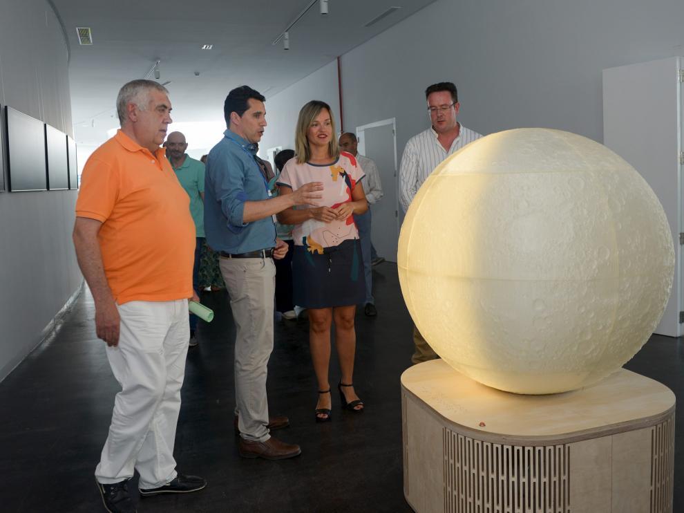 El director del Cefca, Javier Cenarro, explica a la consejera Pilar Alegría la réplica de la Luna en Galáctica.