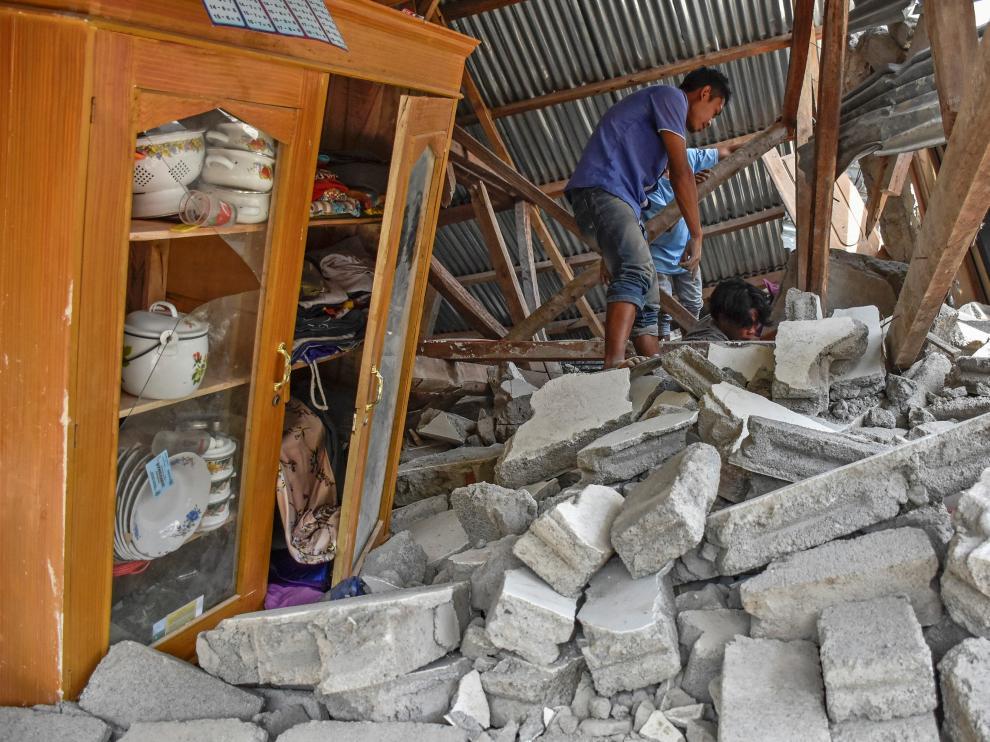 Un hombre camina a través de las ruinas de lo que fue su casa