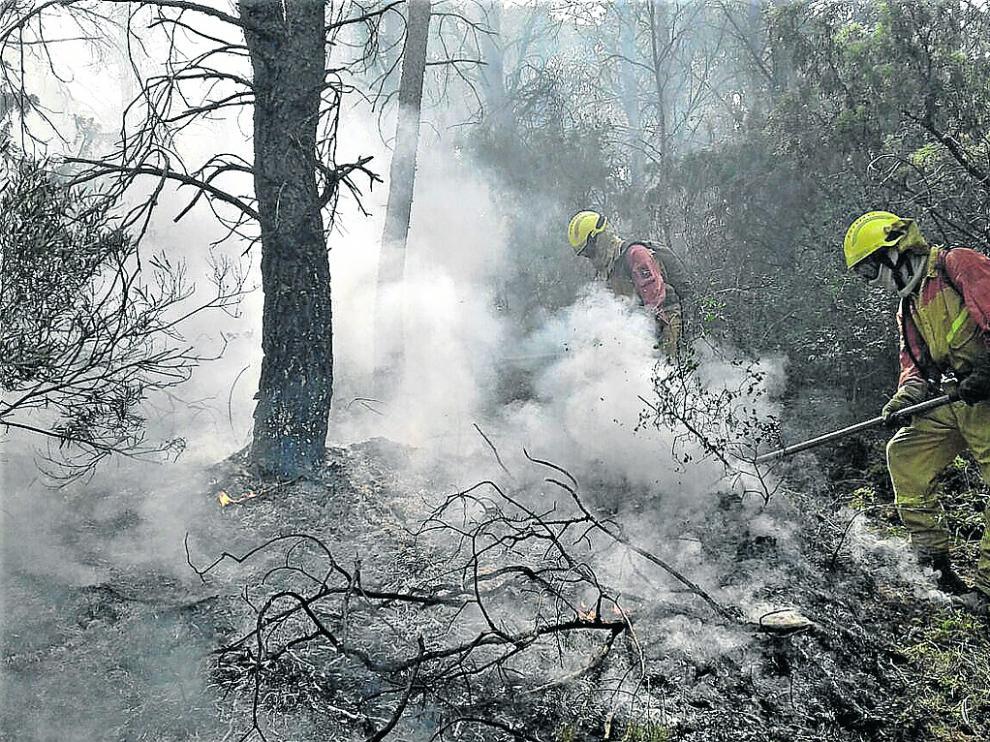 Miembros del operativo de extinción de incendios apagan un fuego causado por un rayo en Zuera