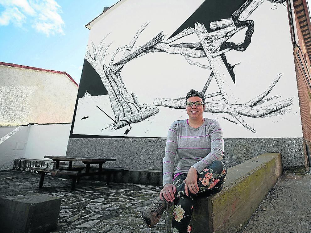 La alcaldesa de Aladrén, Marta Blanco, ante uno de los murales del municipio.