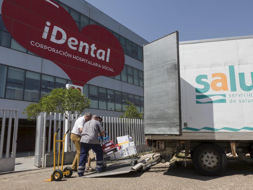 Unos operarios suben a la furgoneta del Salud los expedientes clínicos de los pacientes de Idental