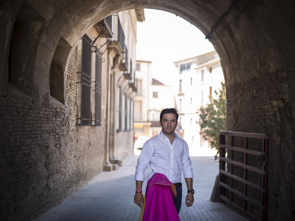 Imanol Sánchez posa con su capote en la calle Velasco, en el acceso a la plaza de España, junto al palacio de los Duques de Villahermosa.