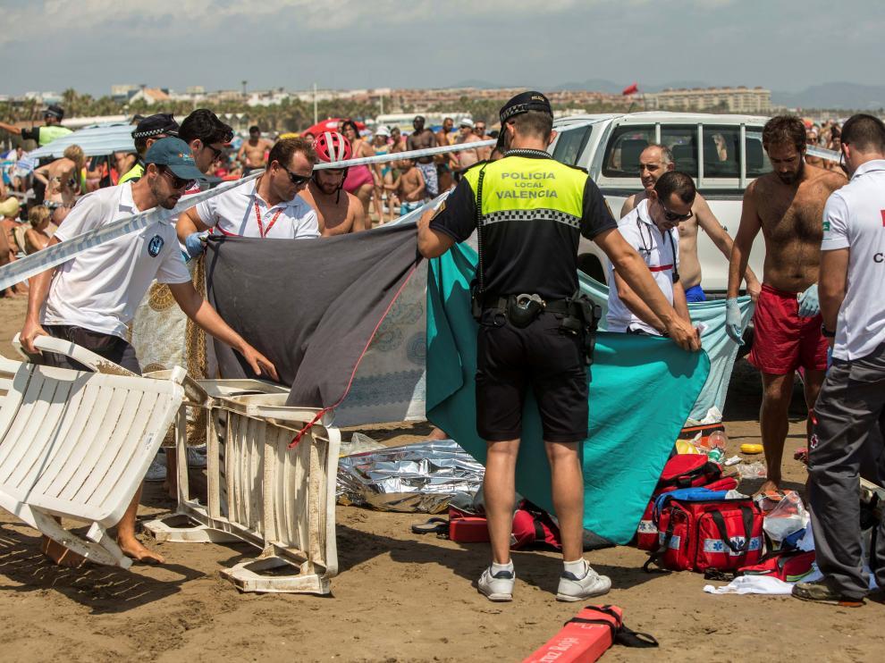 Miembros de la Cruz Roja, junto al cuerpo de un hombre que se ha ahogada en aguas de la playa de la Malvarrosa, en Valencia.