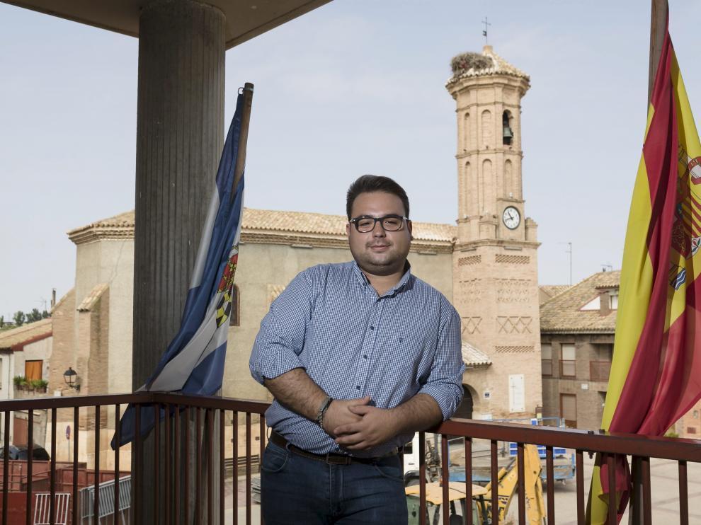 El alcalde, en el ayuntamiento de Pinseque, con la iglesia de San Pedro Mártir al fondo.