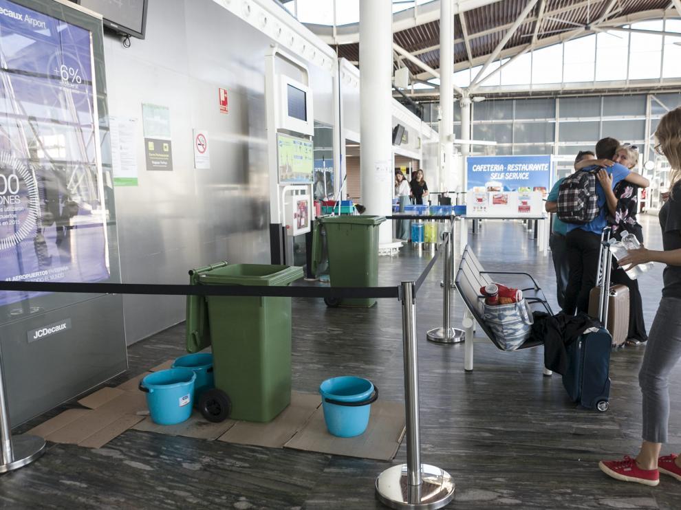 Varios pasajeros, ayer junto a los cubos utilizados para recoger el agua de las goteras