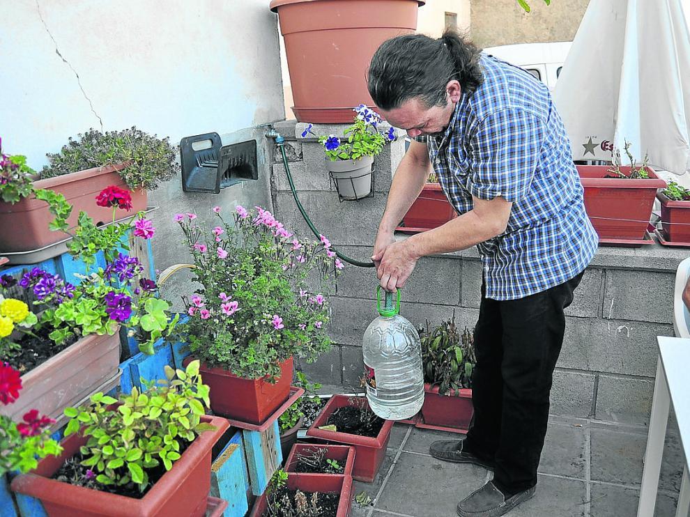 Un vecino de Cretas, llenando garrafas para tener una mínima reserva de agua en el bar que regenta.