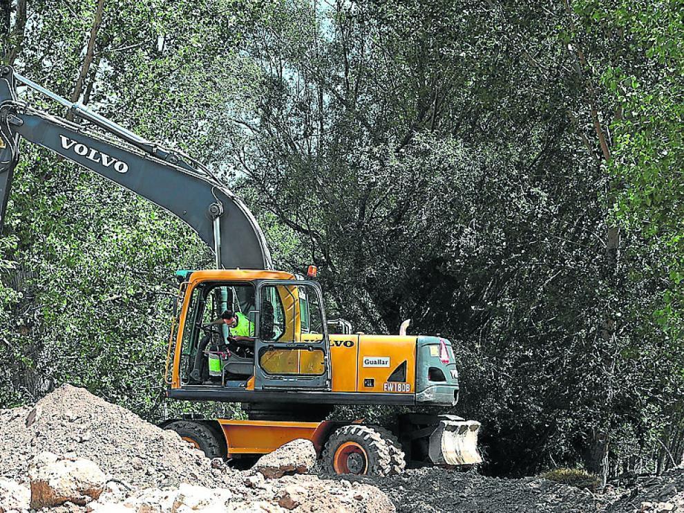 La excavadora retira los depósitos para abrir paso al río.