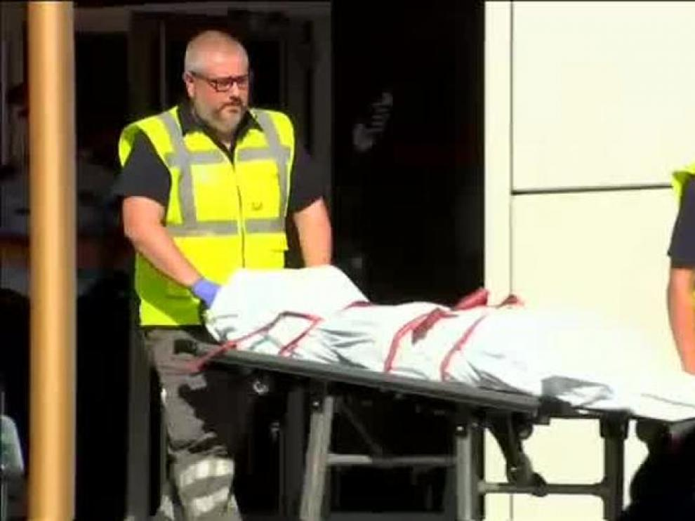 Momento del levantamiento del cadáver del hombre abatido en la comisaría de Cornellà