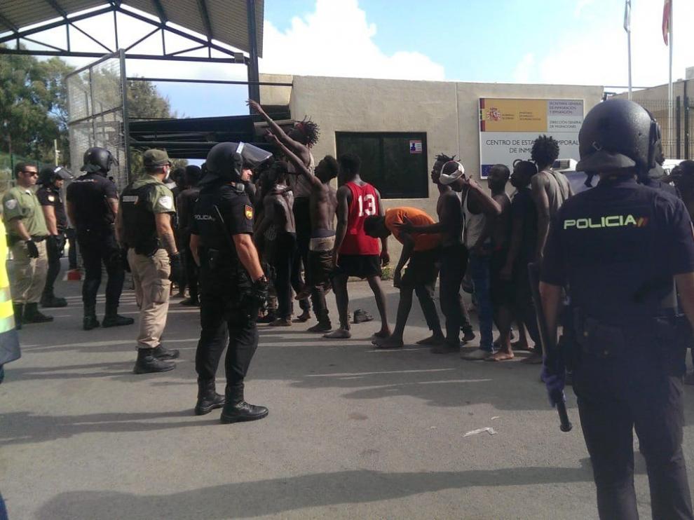 Varios inmigrantes custodiados por efectivos de la Policía Nacional.