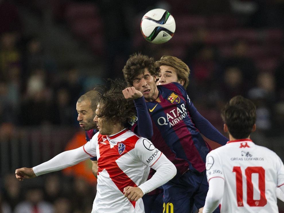 Juan Esnáider en una disputa aérea con Mascherano y Sergi Roberto en el partido de Copa del Rey que el Huesca, de Segunda B, jugó en el Camp Nou en diciembre del 2014.