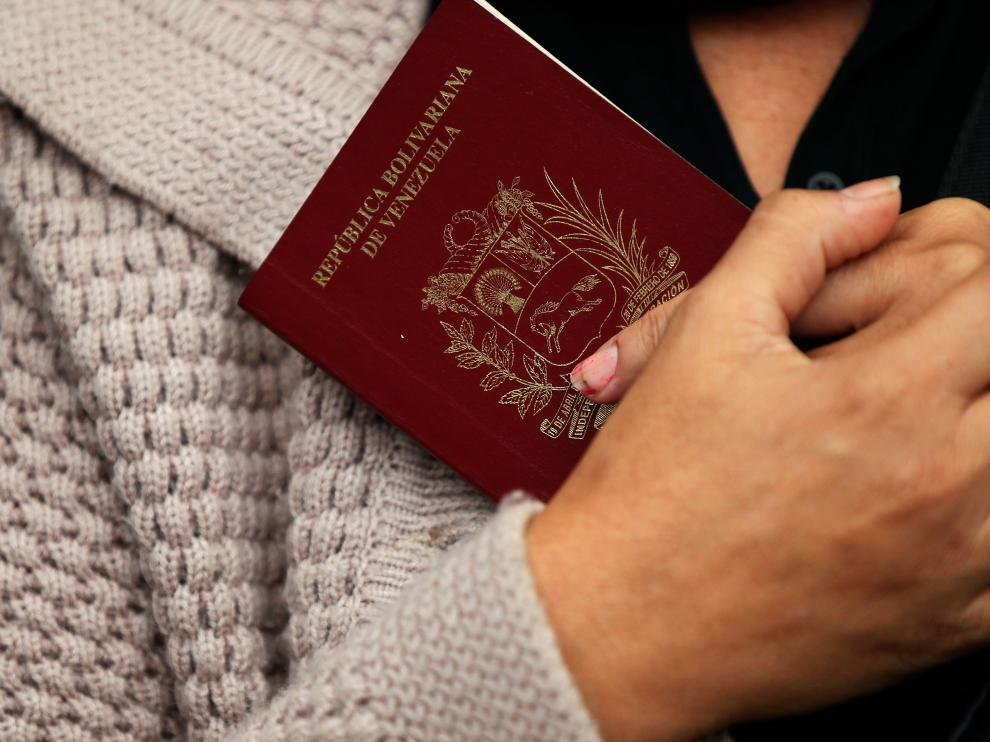 Una mujer venezolana sostiene su pasaporte a la espera de cruzar el paso fronterizo entre Ecuador y Perú.