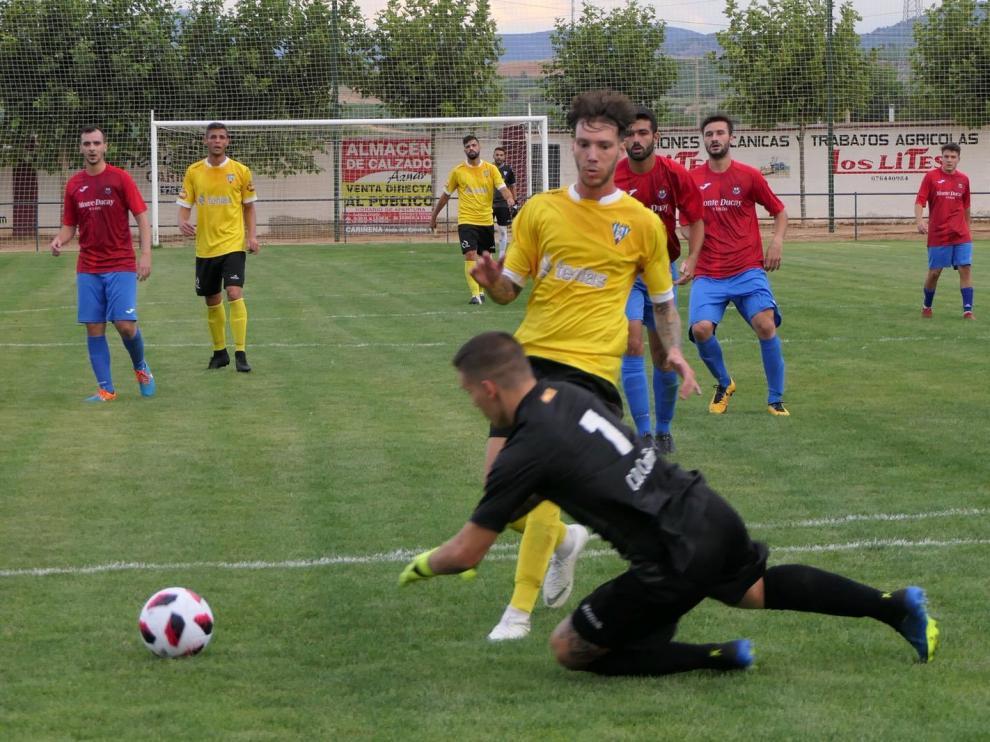El jugador del Ejea Héctor Otín intenta salvar al portero del Cariñena en un partido amistoso de pretemporada