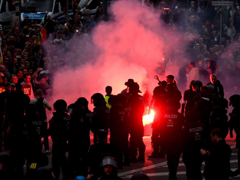 Manifestantes de derecha prenden bengalas mientras enfrentan a la policía antidisturbios en Chemnitz (Alemania).