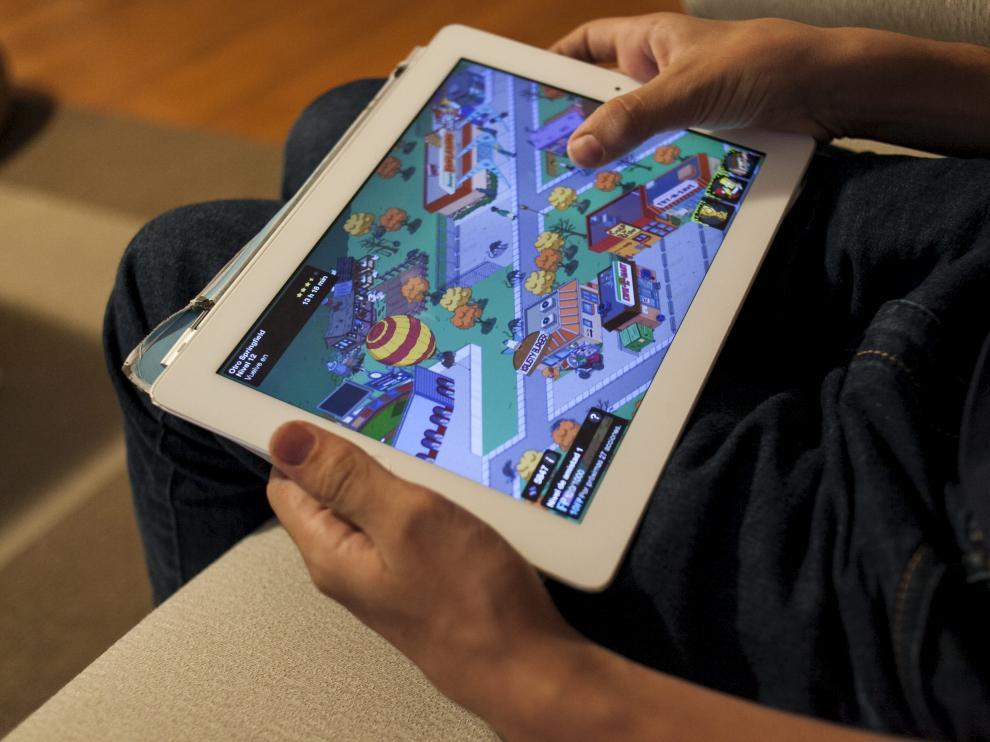 Un joven con una tablet jugando
