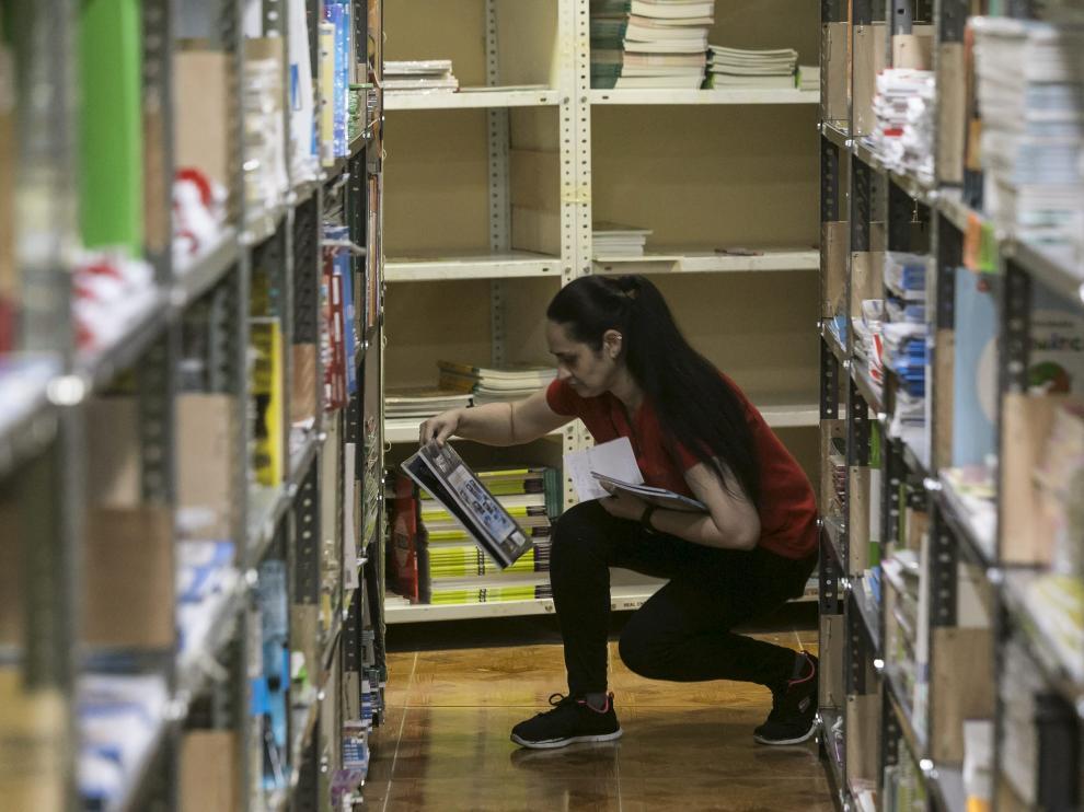 Una empleada de la Librería Central de Zaragoza selecciona entre los estantes libros para el curso en ciernes.