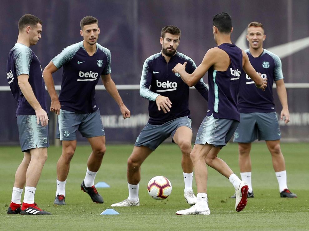 Varios jugadores del Barcelona, entre ellos el central Piqué, durante el entrenamiento de este sábado en la Ciudad Condal.