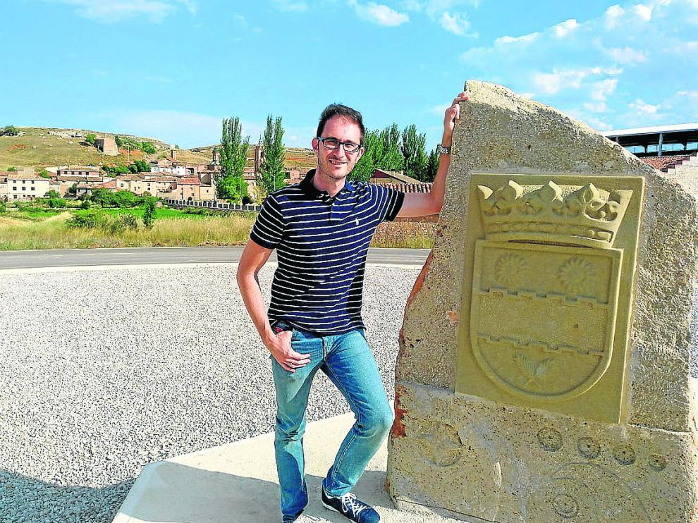 El alcalde, en la rotonda de entrada a Villarroya del Campo, con el escudo del pueblo.
