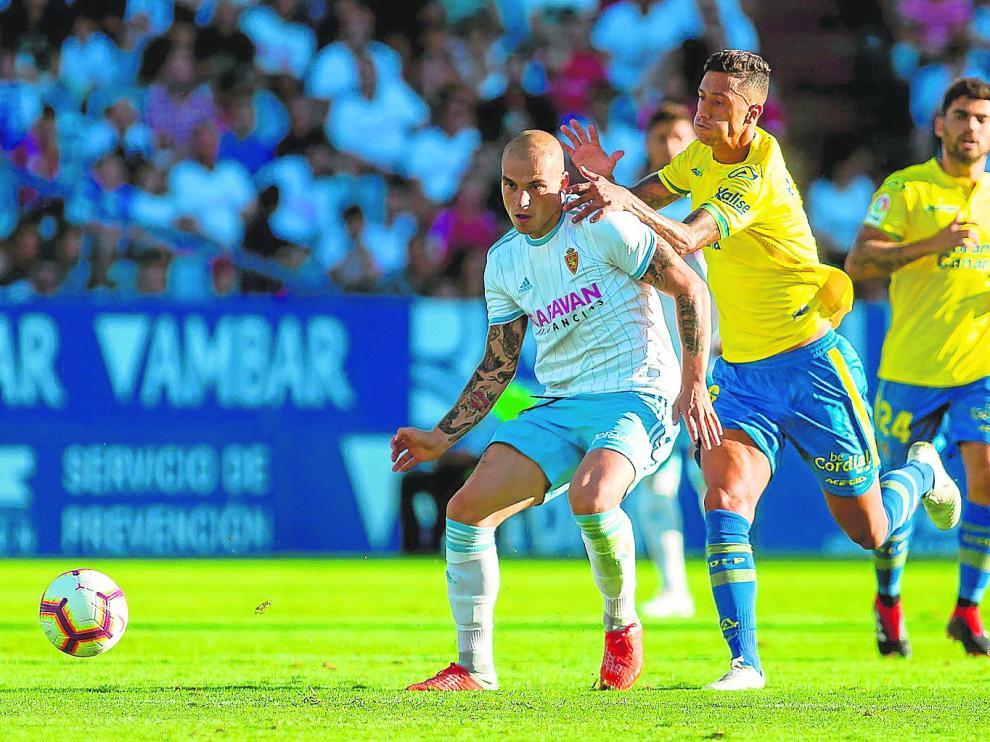 Maikel Mesa, de Las Palmas, trata de frenar infructuosamente a Jorge Pombo.