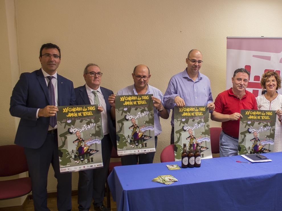 Los organizadores del concurso de tapas de jamón de Teruel, posan con el cartel anunciador.