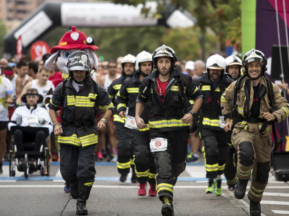 Imagen de los bomberos, con el equipo a cuestas, durante la 10K Bomberos de Zaragoza.