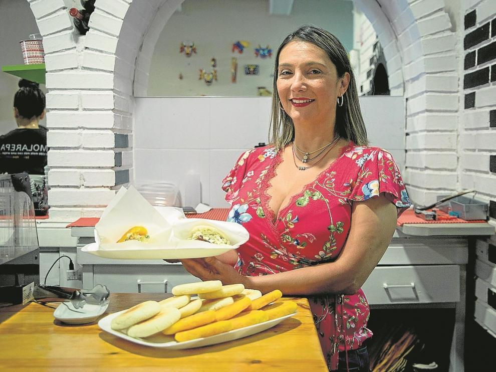 Mayori, con dos platos de arepas, algunas de ellas rellenas, en el bar Molarepa.