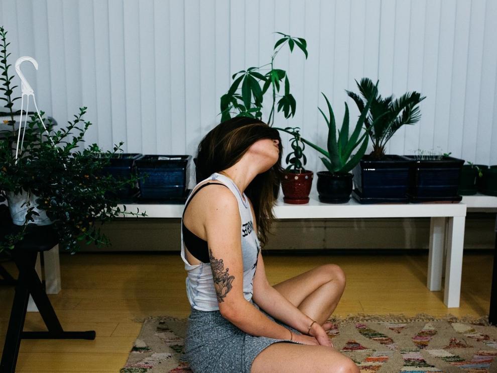Una joven realiza técnicas de relajación sentada en el suelo.