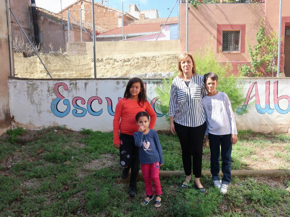 María Pilar, Khadija, la profesora Mariví y David, en el patio de la escuela de Alba.