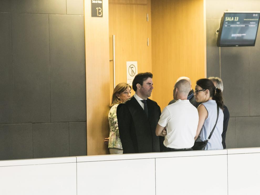 El acusado, de espaldas con un polo blanco, escuchando por poca de su abogado, Marco Antonio Navarro, los términos del acuerdo.