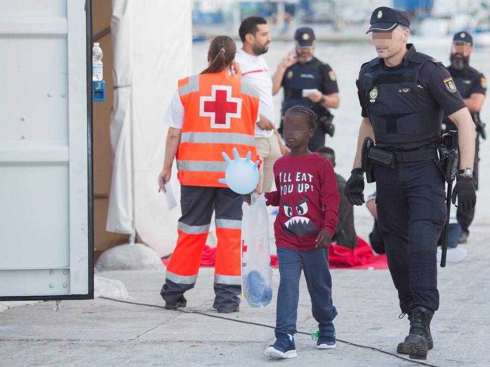 Uno de los menores rescatados junto a un Policía Nacional en el puerto de Málaga