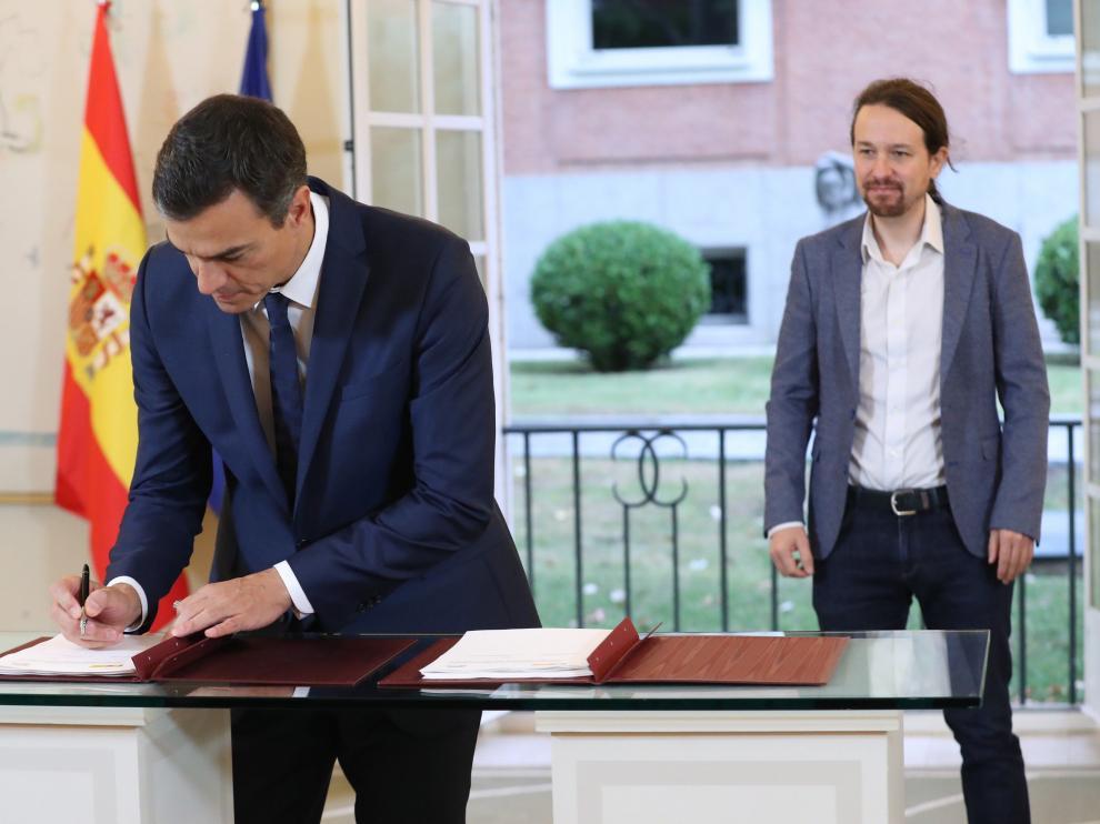Sánchez e Iglesias firmando el acuerdo presupuestario en Moncloa.