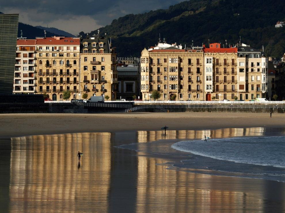 Un surfista camina por la playa de la Zurriola de San Sebastián, donde las temperaturas van a superar los veinte grados en las horas centrales del día. El tiempo previsto para hoy en Euskadi es de cielos poco nubosos o despejados con intervalos de nubes medias y altas, posibles brumas matinales en Álava, temperaturas en ascenso, más acusado el de las mínimas, y viento flojo del sur que subirá en intensidad al final del día en Gipuzkoa y en el extremo oeste de Bizkaia.-