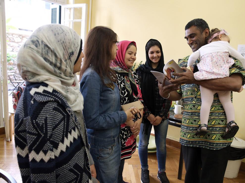 El secretario general de AI sostiene en sus brazos a una bebé inmigrante en un centro de mujeres de Atenas.