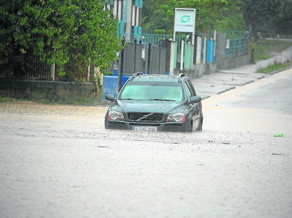 Un coche, atrapado por el agua acumulada en el polígono industrial Sepes de Huesca.