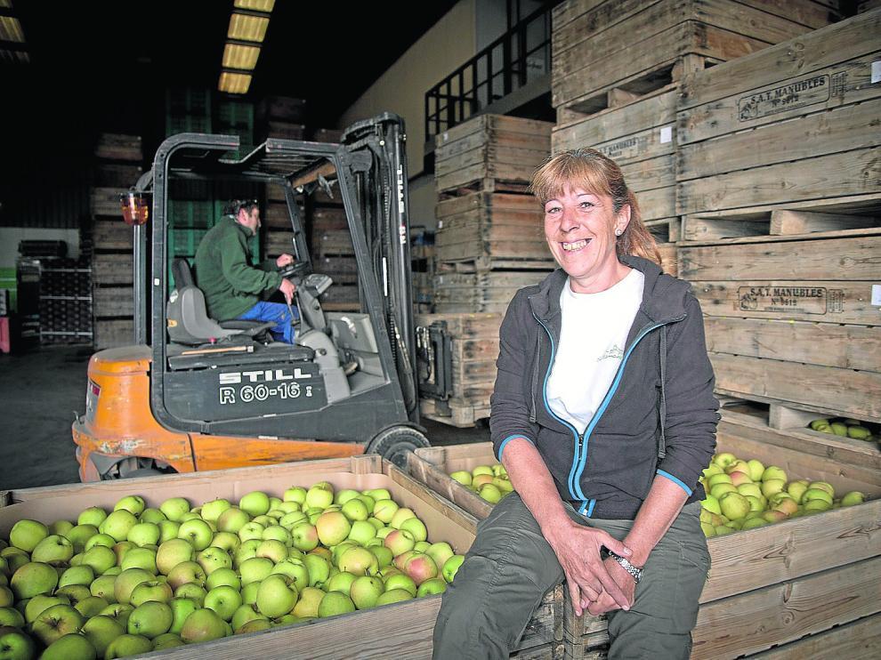 La agricultora Fina Martínez sonríe junto a las manzanas recolectadas
