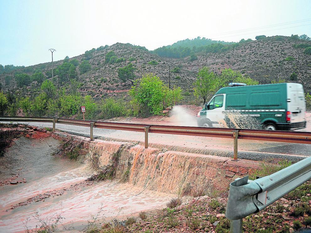 Una torrentera anega y cruza la carretera N-330, también cortada por la caída de rocas, entre Teruel y Villastar.