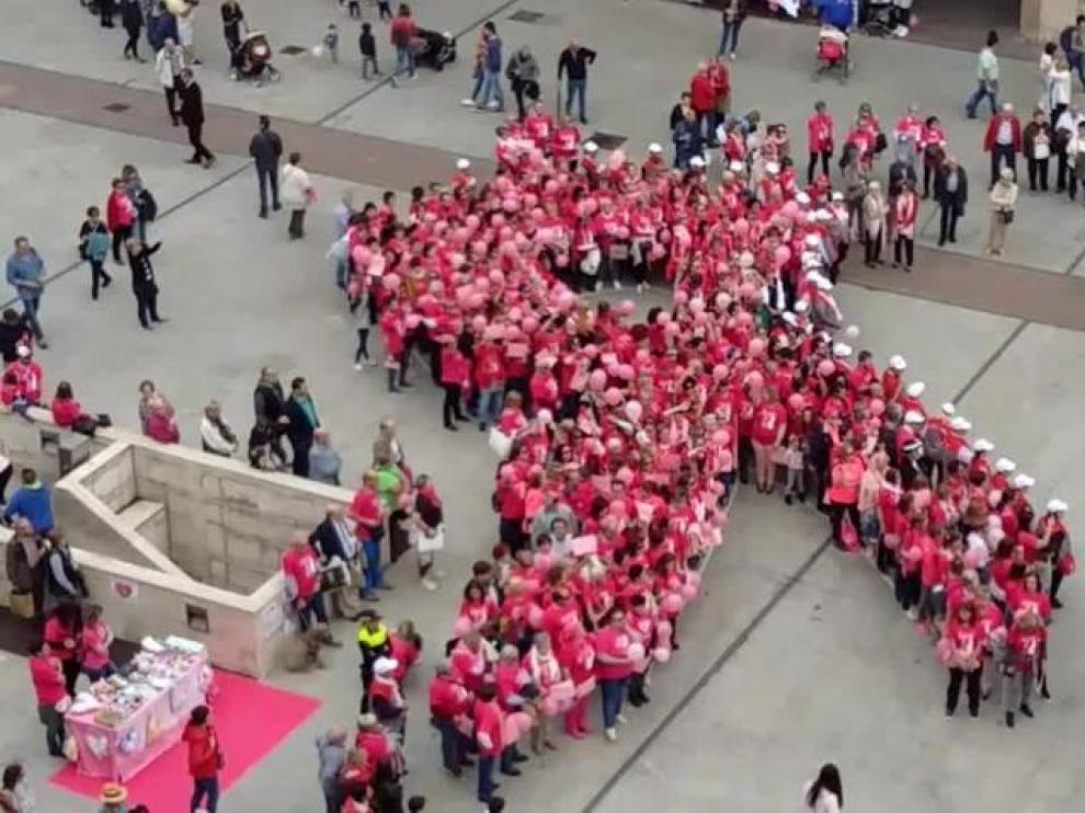 Un gran lazo humano rosa, símbolo de lucha contra el cáncer de mama