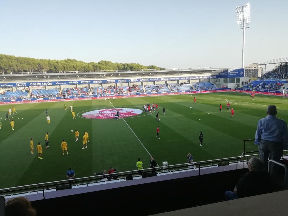 Los jugadores de ambos equipos rematando el calentamiento sobre el verde de El Alcoraz.