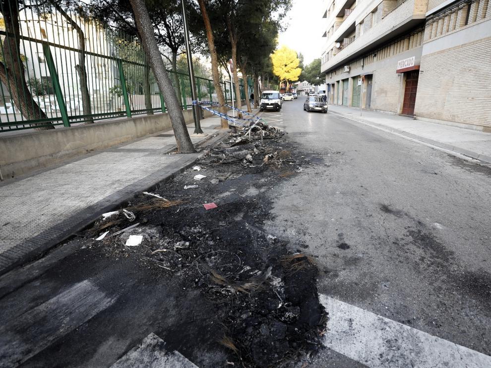 Restos del contenedor y el vehículo quemado en la calle de San Eugenio en Torrero.