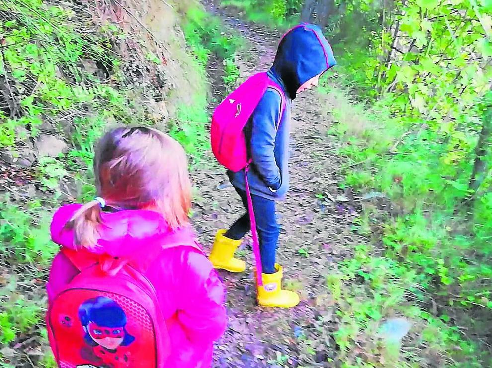 Laia y Aran se dirigen por una senda al colegio de Olba ante la imposibilidad de llegar en coche