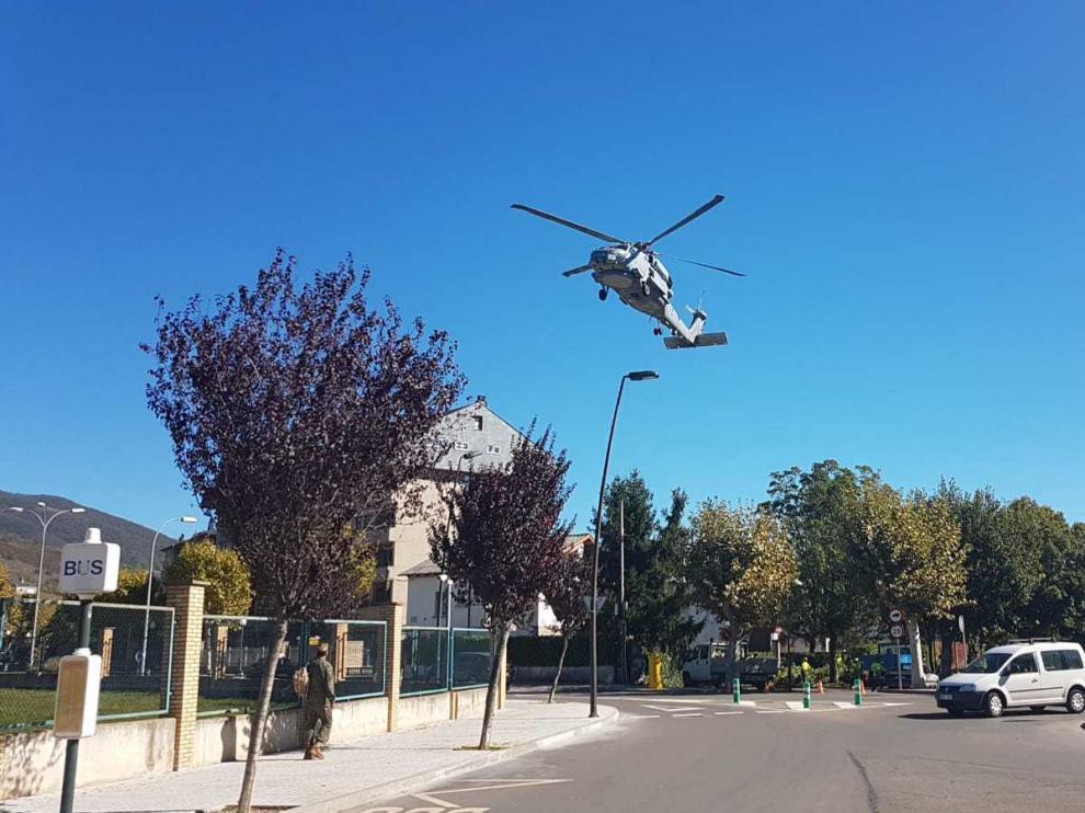 Un helicóptero aterrizando en la Escuela Militar de Jaca y pasando por encima del árbol cuya rama ha caído sobre dos mujeres