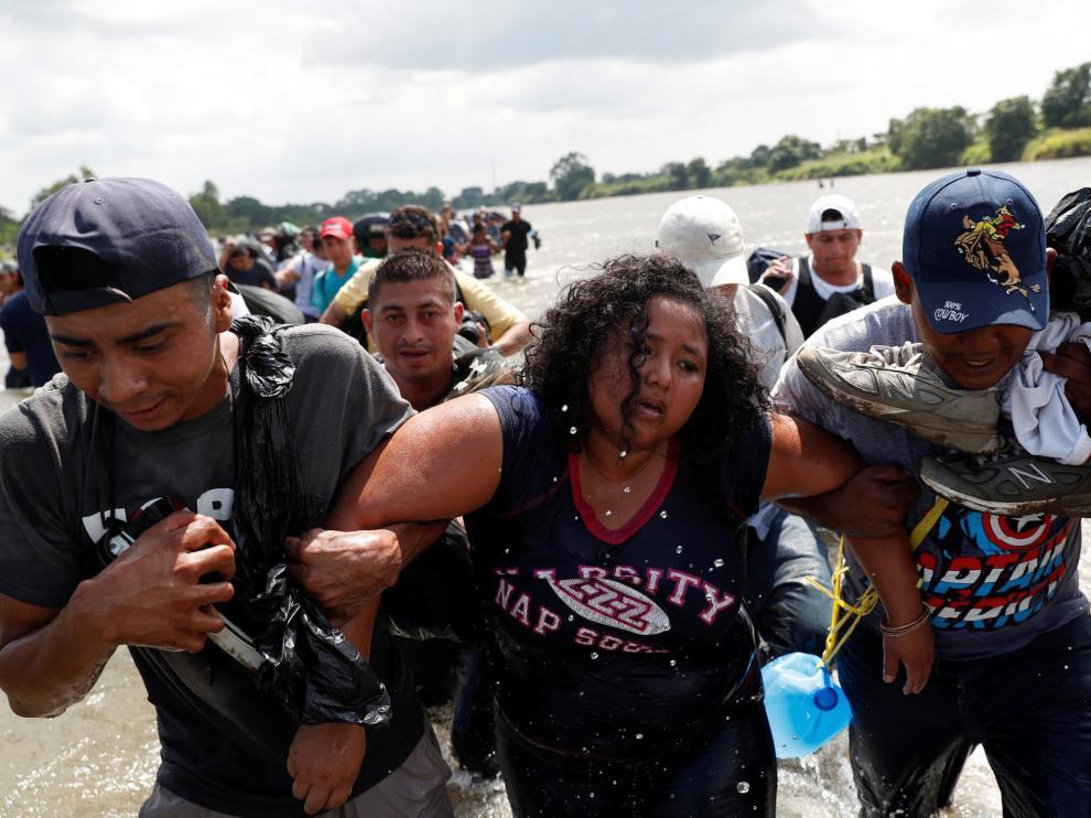 Una mujer es ayudada a cruzar el río Suchiate, en la frontera entre Guatemala y México