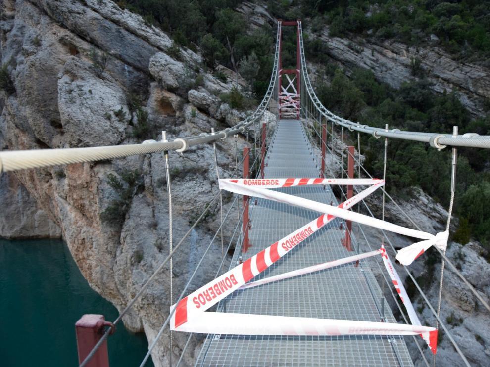 Unas cintas indican que no se puede pasar por el puente que une las dos orillas del congosto.
