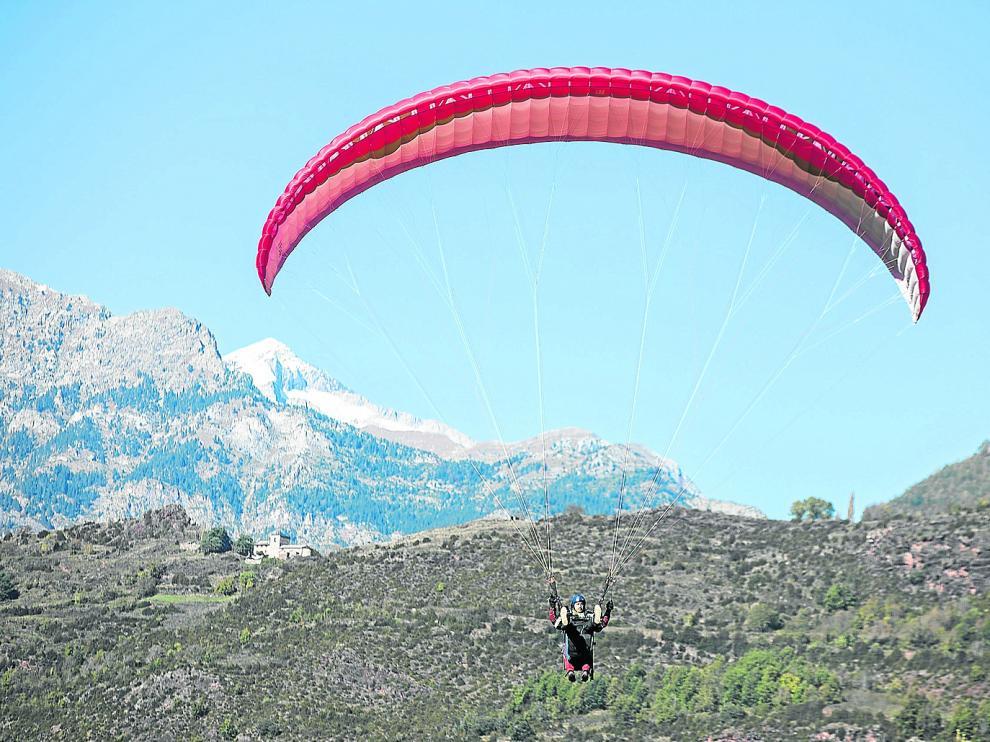 Un parapente biplaza se aproxima a la zona de aterrizaje de La Lleva, en Castejón de Sos.