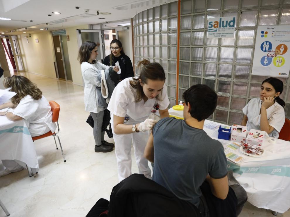 Dos alumnas de Enfermería de la Universidad de Zaragoza vacunan a uno de sus compañeros