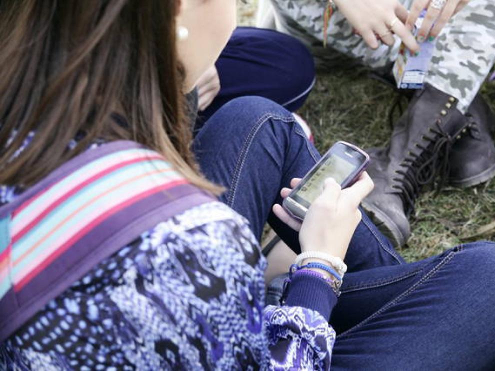 Imagen de archivo de jóvenes usando móviles.