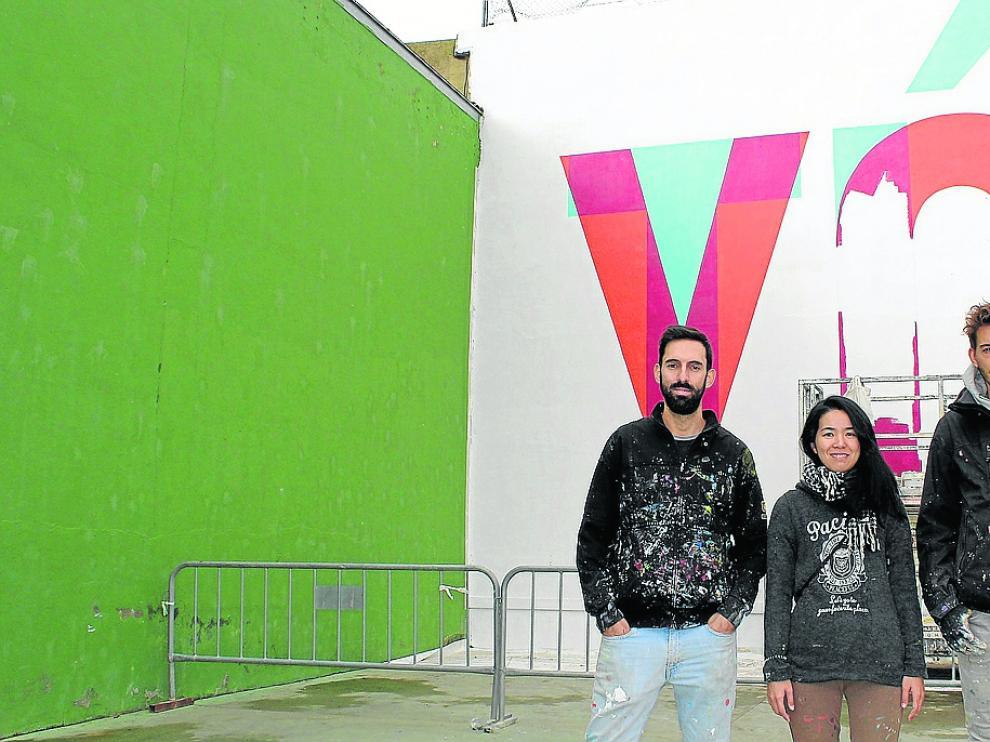 Los artistas de Boa Mistura, ante el mural que han realizado en Grañén.