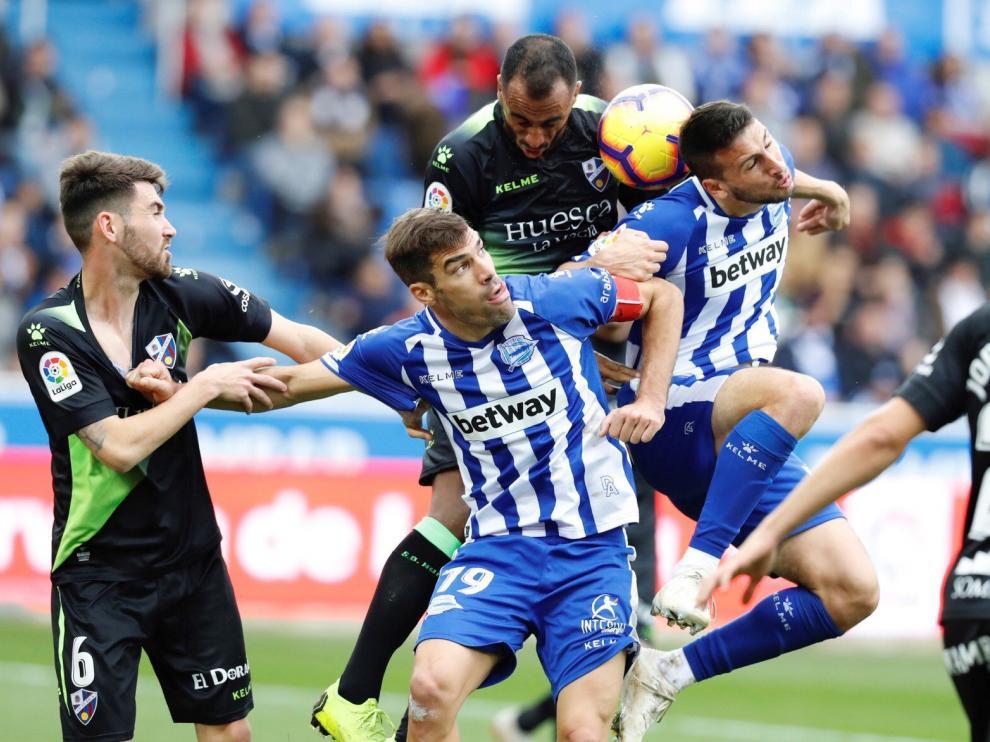 El centrocampista del Huesca Moi Gómez, el defensa del Deportivo Alavés Manu García, el defensa del oscense Carlos Akapo, y el delantero argentino del equipo vasco Jonathan Calleri (i a d) durante el partido correspondiente a la décima segunda jornada de Liga de Primera División disputado hoy en el estadio Mendizorrotza de Vitoria.