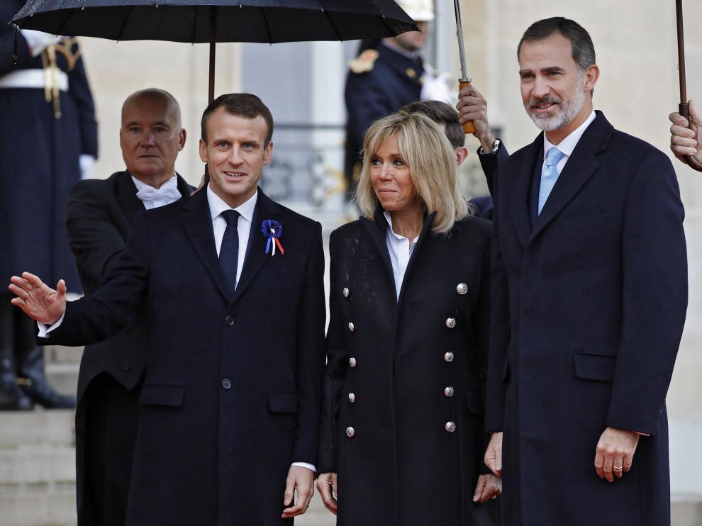 Emmanuel y Brigitte Macron, con el rey Felipe VI, este domingo en París.