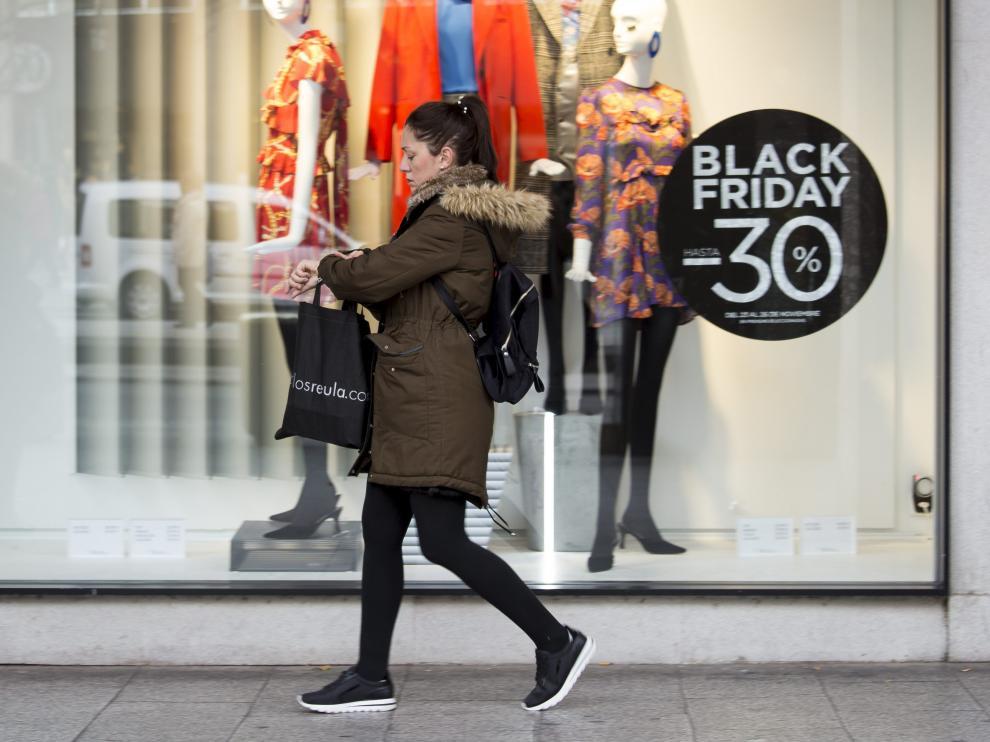Una mujer pasa frente a un escaparate durante un 'Black Friday'.